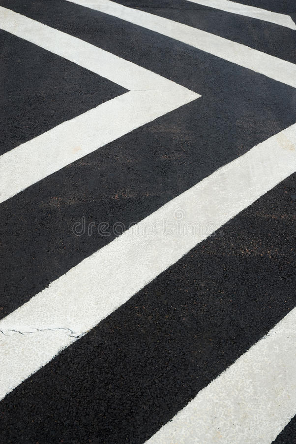 White chevron lines on a speed bump. White chevron lines on a black section of tarmac to slow traffic down royalty free stock photo