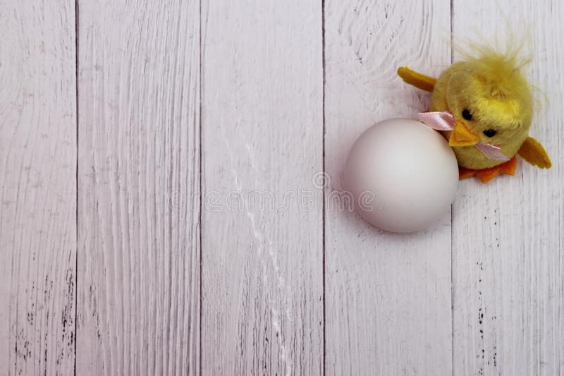 White chicken egg is located next to funny yellow fluffy toy chicken. The concept of the Easter holiday. Empty space. White chicken egg is located next to funny royalty free stock photos