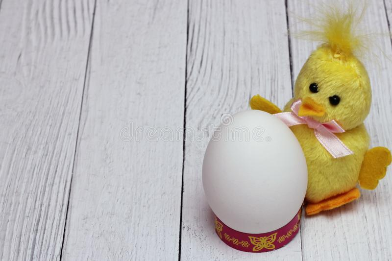 White chicken egg is located next to funny yellow fluffy toy chicken. The concept of the Easter holiday. Empty space. White chicken egg is located next to funny stock photo