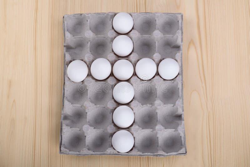 White chicken eggs as a cross stock photo