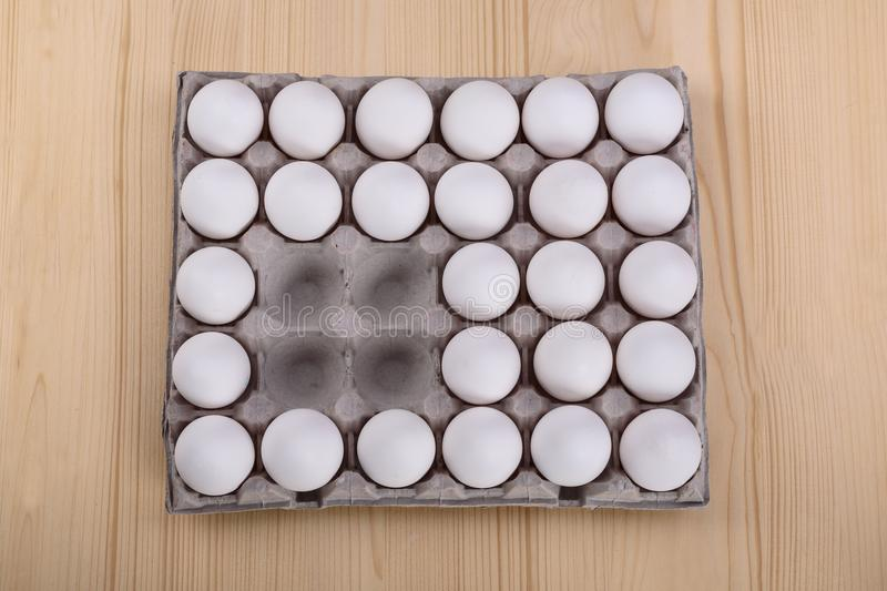 White chicken eggs in a cardboard box with empty cells stock images