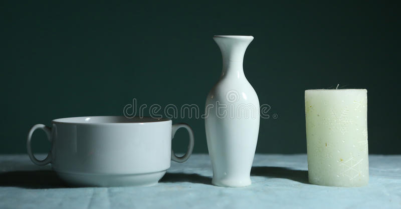 White china jar bowl and candle still life. On blue background royalty free stock photos