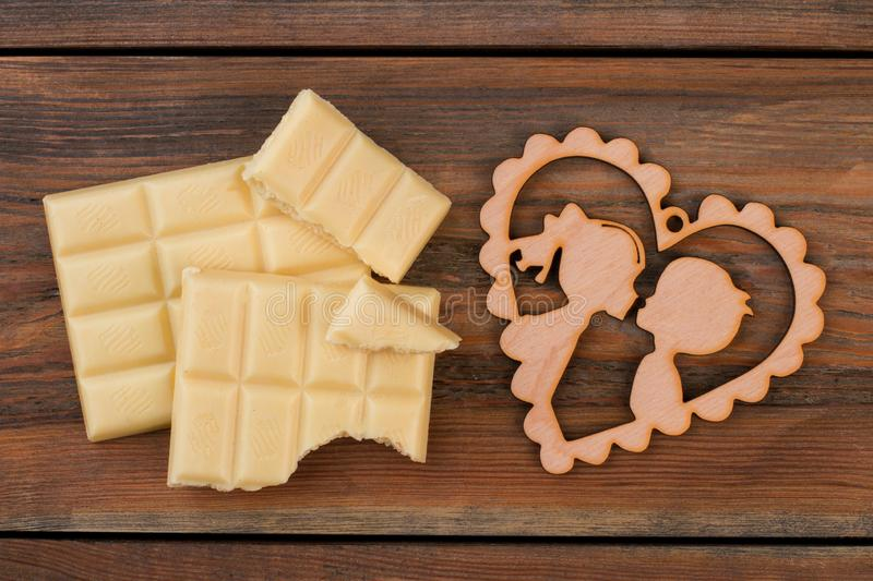 White chocolate bars and heart shaped wooden figure. Chocolate pieces and plywood heart on rustic wooden background stock images