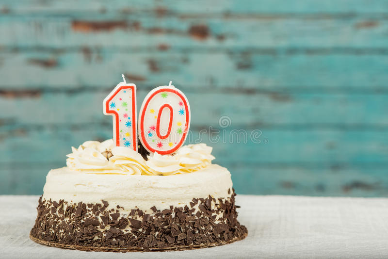 White and chocolate cake with ten candles. Frosted cake with the 10 candles for a tenth birthday or anniversary royalty free stock photos