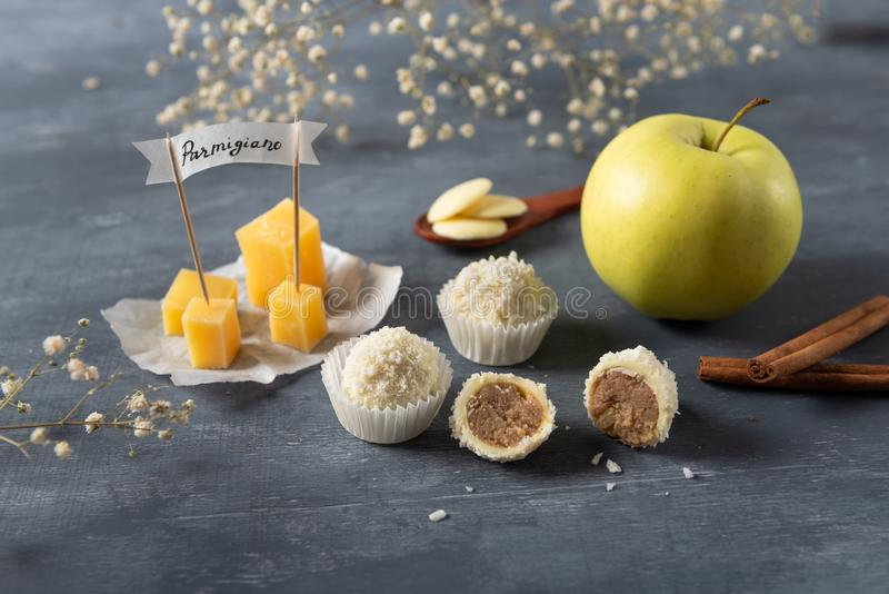 White Chocolate candies with cheese, parmisan, apple and cinnamon on the background. Delicious candies for gourmet stock photo