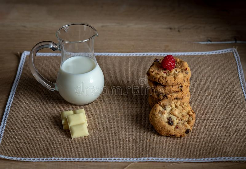 White chocolate cookies and jug of milk delicious traditional stock photo