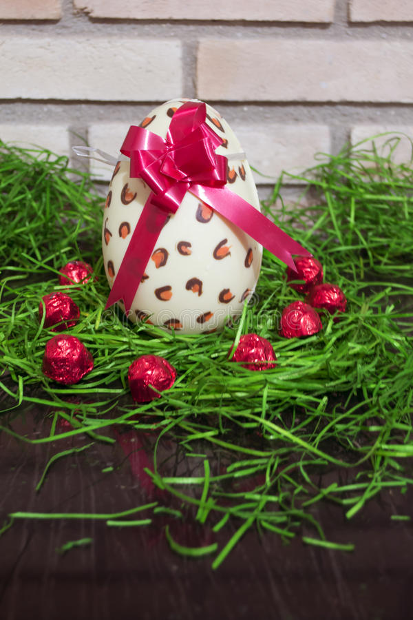 White chocolate Easter egg with red lace and brick 4 royalty free stock image