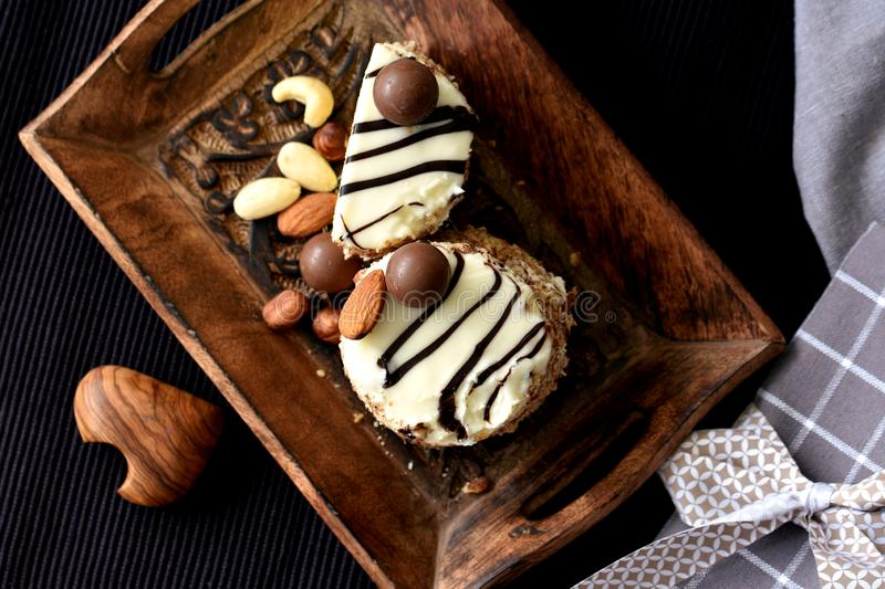 White chocolate and nuts keto dessert on rustic tray. One and half white chocolate and nuts keto dessert served on dark wooden tray, decorated with almonds and royalty free stock images