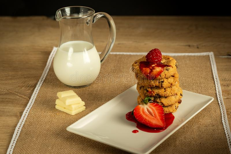 White chocolate and raspberry, chocolate chip cookies and milk jug strawberry syrup stock images