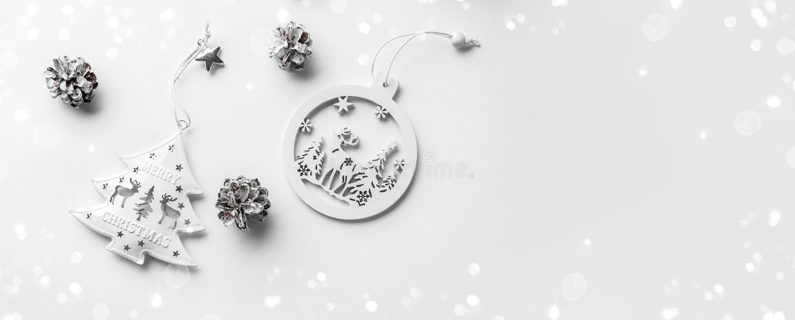White Christmas decoration on white background with pine cones. Xmas and Happy New Year theme, bokeh, light. Flat lay, top view, wide composition royalty free stock image