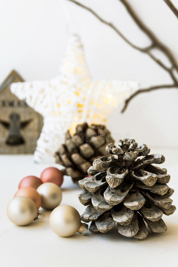 White Christmas decoration composition, big pine cones, scattered baubles, shiny star, wooden candle holder, dry tree branches. In background, closeup royalty free stock photo