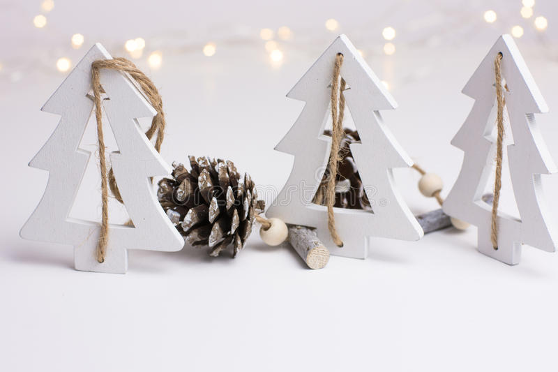 White Christmas decoration in scandinavian style with wood fir trees and pine cones, bokeh lights in the background royalty free stock photos