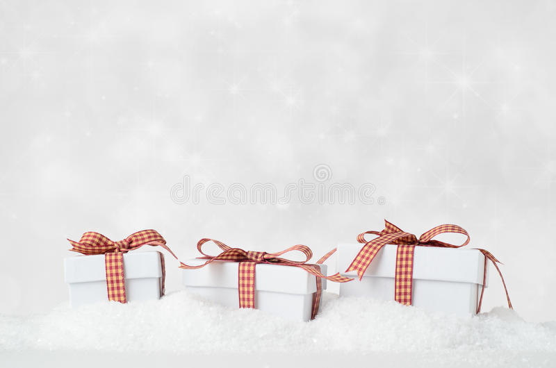 White Christmas Gift Boxes in Snow with Bokeh Background royalty free stock photos