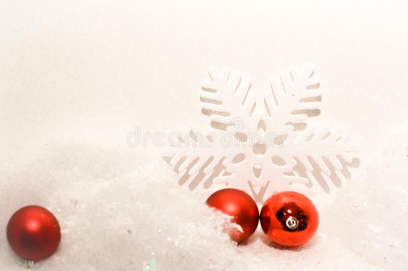 Christmas Background with White Snowflake and Red Ornaments. A white Christmas holiday, winter background with a white snowflake and three red ball Christmas stock images