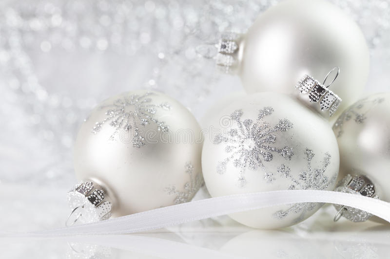 White Christmas Ornaments. With snowflake detail with bokeh sparkly silver and white background royalty free stock images