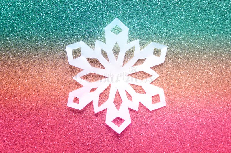 White Christmas paper snowflake on gradient colored backgound royalty free stock image