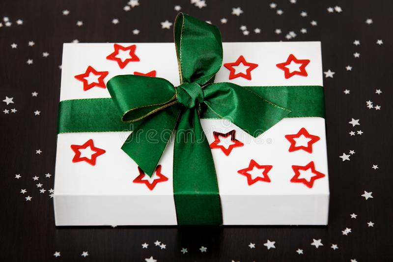 White Christmas present box with red stars and a green ribbon, lying on a dark table, surrounded by small silver stars. royalty free stock image