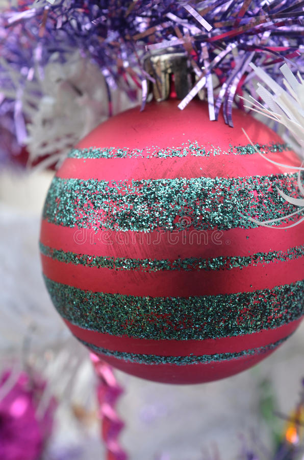 White Christmas red ball ornament with sliver glitter stipes. Close up view a vintage metal red Christmas tree ornament with silver glitter stripes stock image