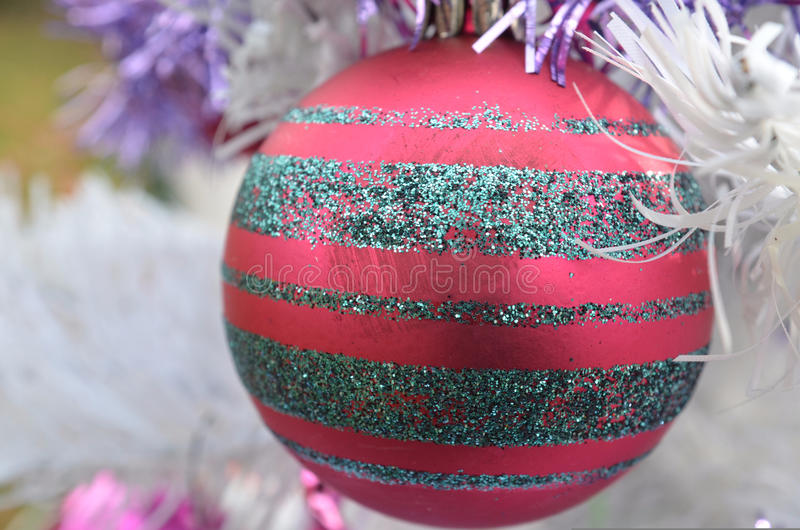 White Christmas red ball ornament with sliver glitter stipes. Close up view a vintage metal red Christmas tree ornament with silver glitter stripes stock photos