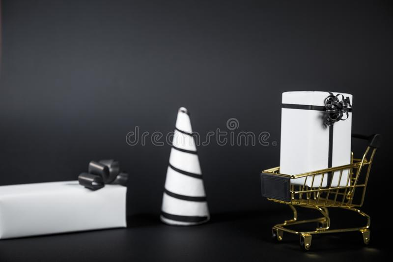 White Christmas tree and gift in shop cart isolated on black background. Copy Space For Advertisement stock images