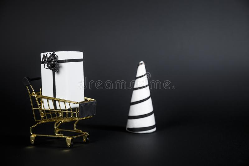 White Christmas tree and gift in shop cart isolated on black background. Copy Space For Advertisement royalty free stock photos