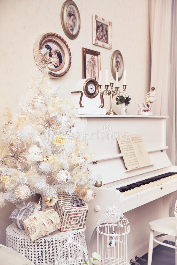 White Christmas tree with hand made ornaments and white piano. Winter time. New Year holiday. royalty free stock images