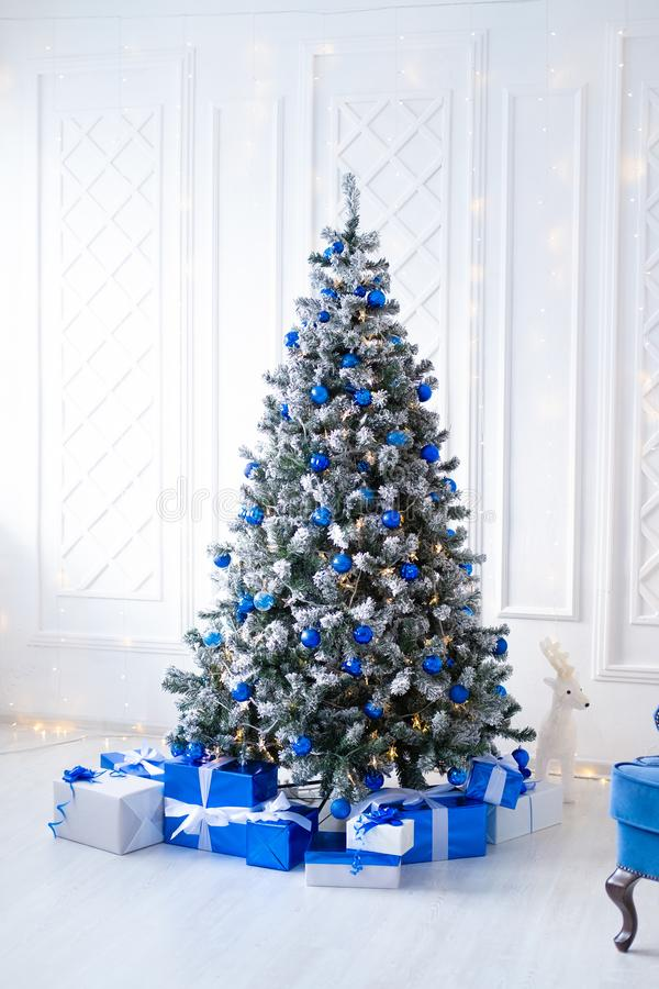Free White Christmas Tree On White, Decorated With Blue Ornaments And Garland, Lots Of Presents Under The Tree Royalty Free Stock Photo - 134602245