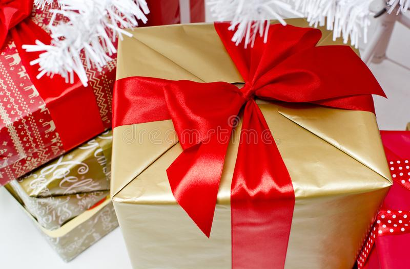 Christmas present for big family. White Christmas tree and presents for big family. Gits in a red and gold color royalty free stock photo