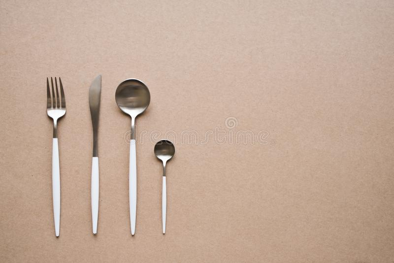 White and chrome cutlery. Set of stylish white and chrome cutlery on beige background, top view, copy space. Table set, menu design stock photos