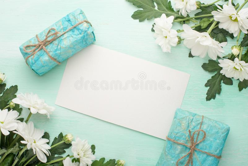 White chrysanthemums with gifts on a wooden background, with empty space for writing or advertising royalty free stock photo