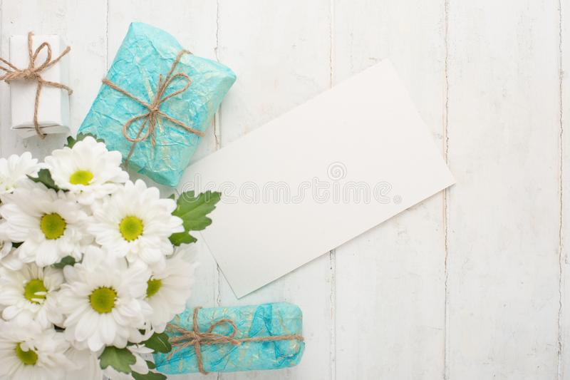 White chrysanthemums with gifts on a white wooden background, with empty space for writing or advertising stock image