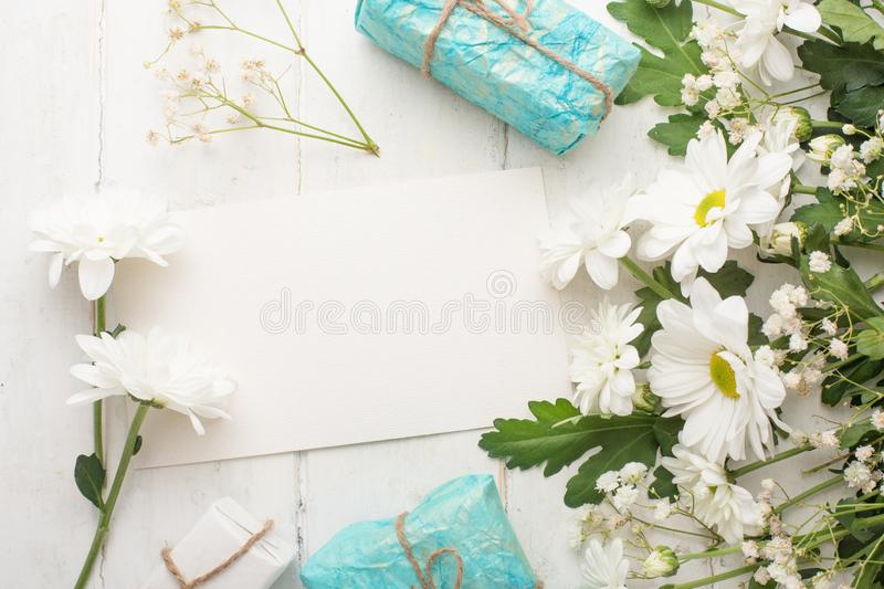 White chrysanthemums with gifts on a white wooden background, with empty space for writing or advertising royalty free stock photography