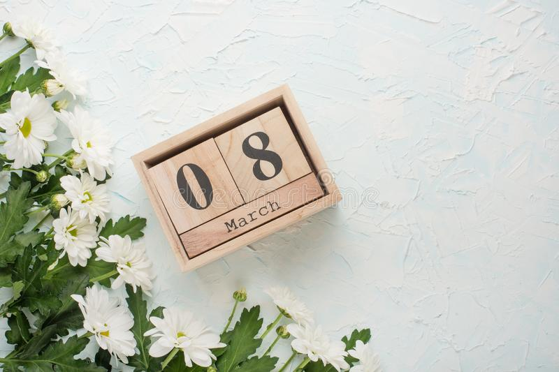 White chrysanthemums on a wooden background with a calendar on which March 8, Mother's Day.  stock photo