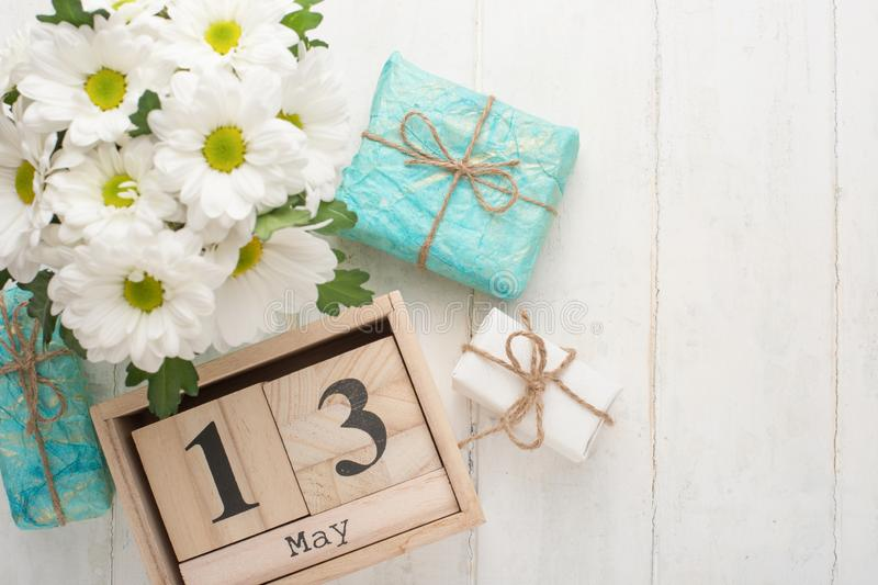 White chrysanthemums on a wooden background with a calendar on which May 13, the International Mother's Day.  stock photos