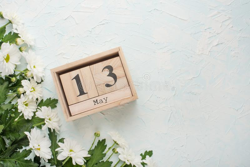 White chrysanthemums on a wooden background with a calendar on which May 13, the International Mother's Day.  stock images