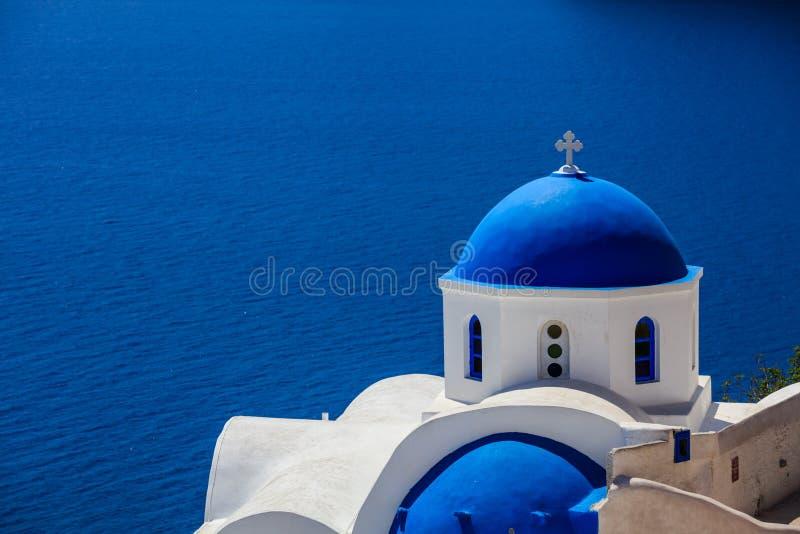 White church with blue dome in Santorini, Greece stock photos