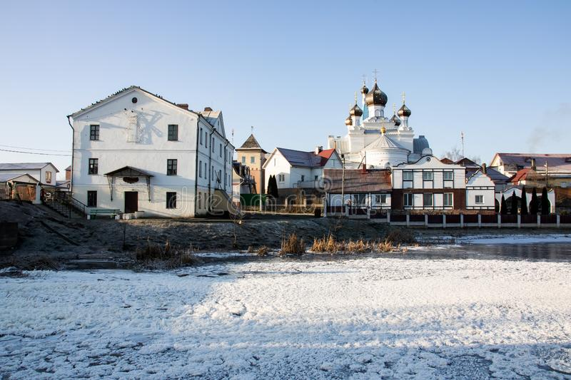 White Church and houses on banks of river, winter landscape royalty free stock photo