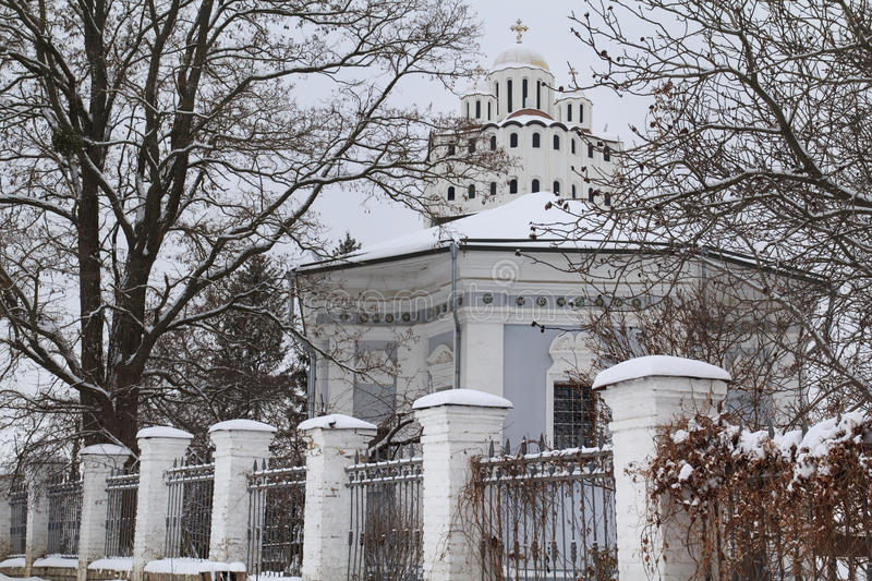 White Church in Snow. White church on a top of the hill with a building and a fence in foreground in snow at winter stock photography