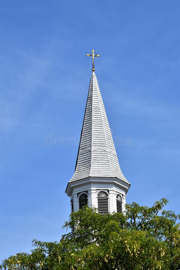 White pointed church steeple and cross in Concord, Middlesex county, Massachusetts, United States. New England Architecture, USA. White pointed church steeple royalty free stock photography