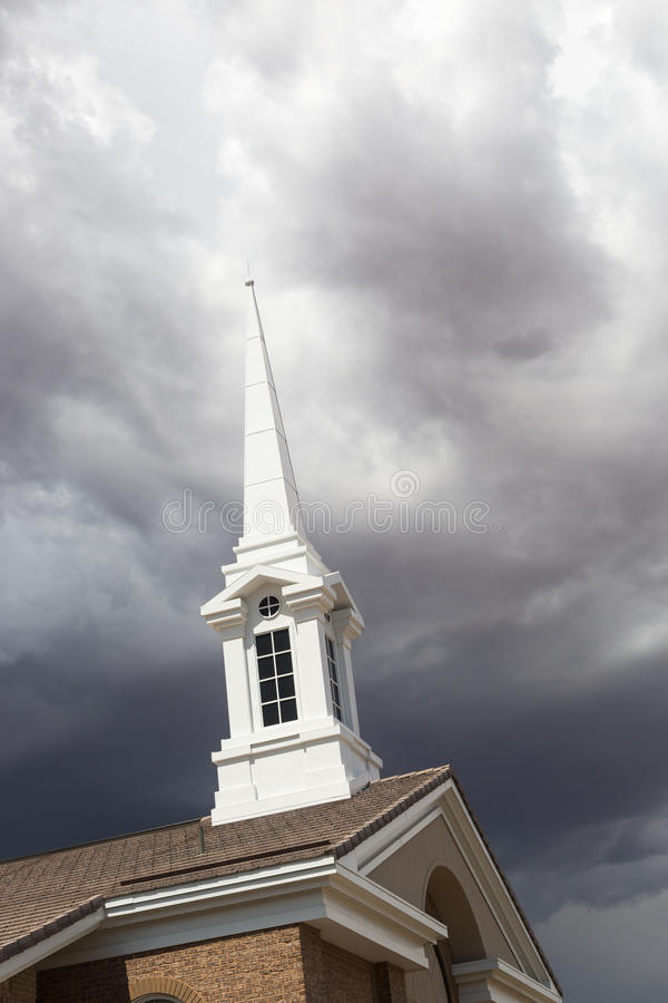 White Church Steeple Tower Below Ominous Stormy Thunderstorm Clouds. Church Steeple Tower Under Ominous Stormy Thunderstorm Clouds stock photos