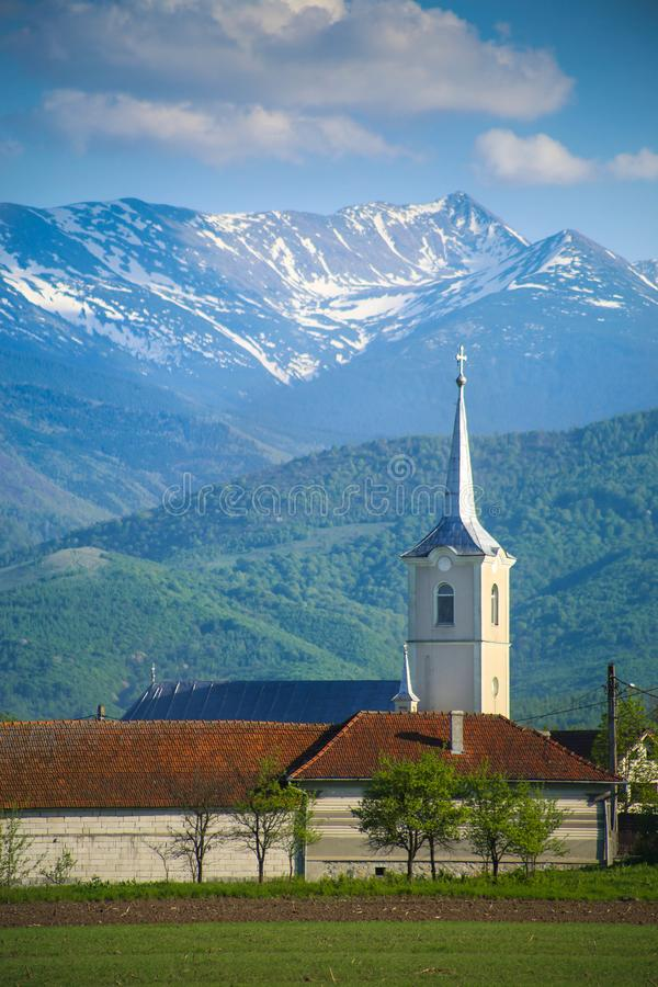 White church tower with corn field foreground and Retezat mountains background in Romania stock photo