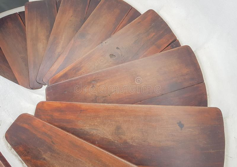 White circular staircase design with dark wood steps. View down. Floor, interior, indoor, brown, architecture, hardwood, construction, decor, clean, stairway royalty free stock image