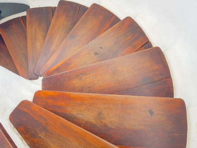 White circular staircase design with dark wood steps. View down. Floor, interior, indoor, brown, architecture, hardwood, construction, decor, clean, stairway royalty free stock photo