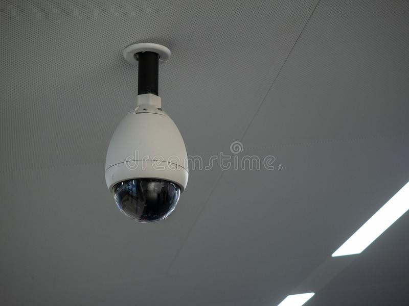 White circular surveillance camera on ceiling in a public setting attached to white ceiling. White circular surveillance camera on ceiling in a public setting on stock images