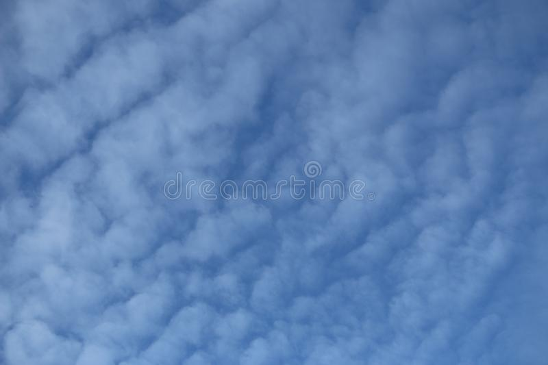 White cirrus clouds against blue sky. light, airy, white, cumulonimbus clouds in bright blue sky on frosty morning. stock image