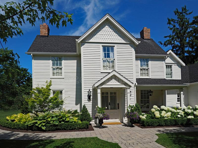 White clapboard house with gable. Generic white clapboard house with gable and hydrangeas stock photography