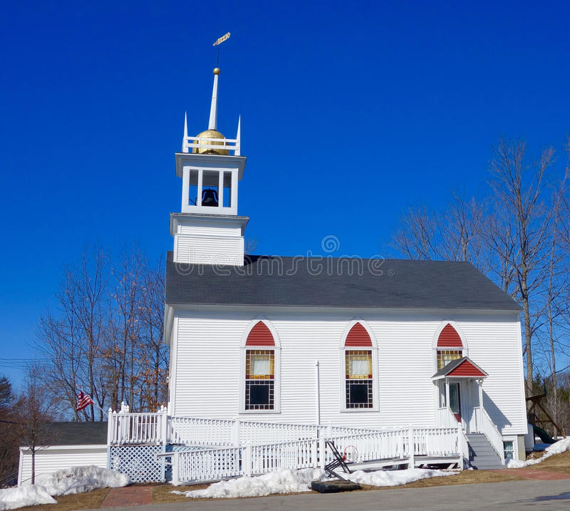 White clapboard New England church in winter. The outside of a church building with bell tower, steeple, gold ball, weathervane, and black and red windows, on a stock photography