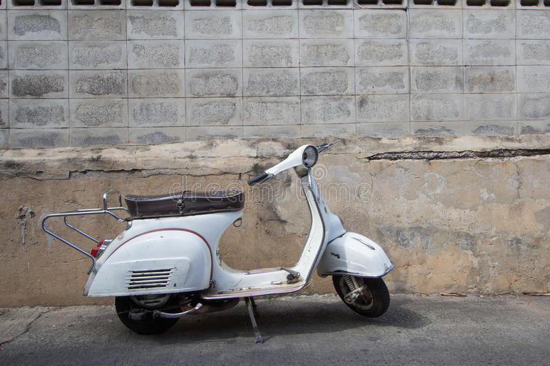 White Classic Vespa scooter stands parked near the concrete old royalty free stock images