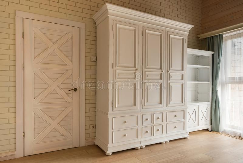 White classic wooden wardrobe. In cottage house royalty free stock image