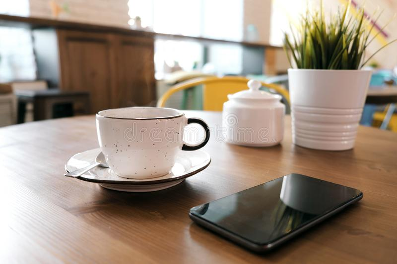 Coffee drink on wooden table with blur cafeteria as background. A white clay cup with coffee stands on a wooden table, next to it is a smartphone and a green royalty free stock photography